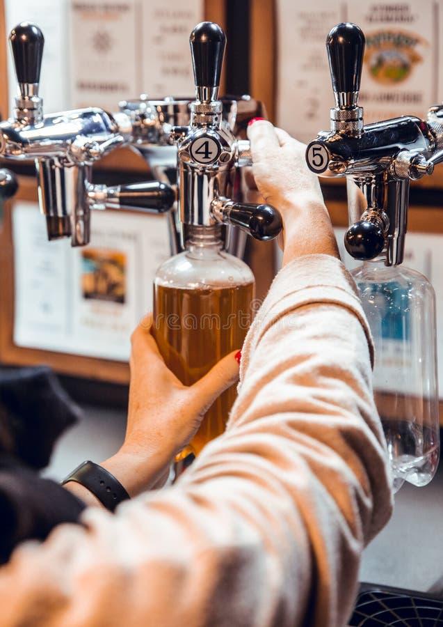Feche acima das mãos da mulher que enchem a garrafa plástica da cerveja do ofício no volume imagens de stock royalty free
