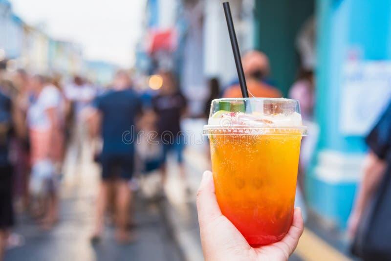 Feche acima das mãos da mulher que guardam o cocktail de fruto no mercado de rua de passeio Phuket tail?ndia imagem de stock