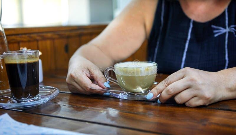 Feche acima das mãos da mulher que guardam um copo de café do cappuccino F?mea com copo de caf? fotos de stock