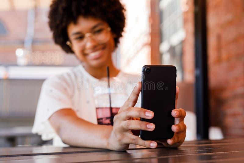Feche acima das mãos da mulher que guardam um smartphone fotos de stock