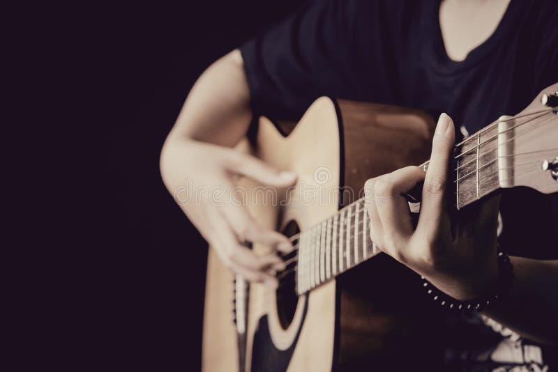 Feche acima das mãos da mulher que jogam a guitarra no fundo escuro imagens de stock