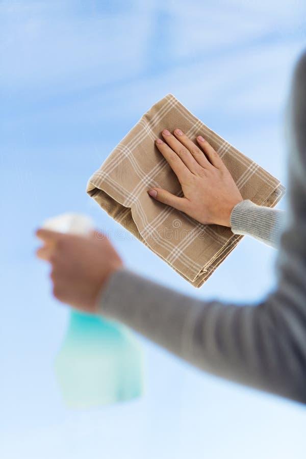 Feche acima das mãos da mulher que limpam a janela com o pano fotos de stock