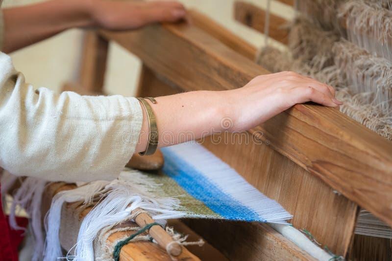 Feche acima das mãos da mulher que tecem o teste padrão azul e branco no tear Técnica de tecelagem tradicional foto de stock
