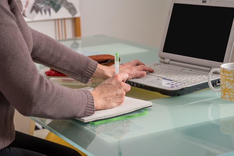 Feche acima das mãos da mulher que trabalham e que estudam em casa com conceito do ensino eletrónico imagens de stock
