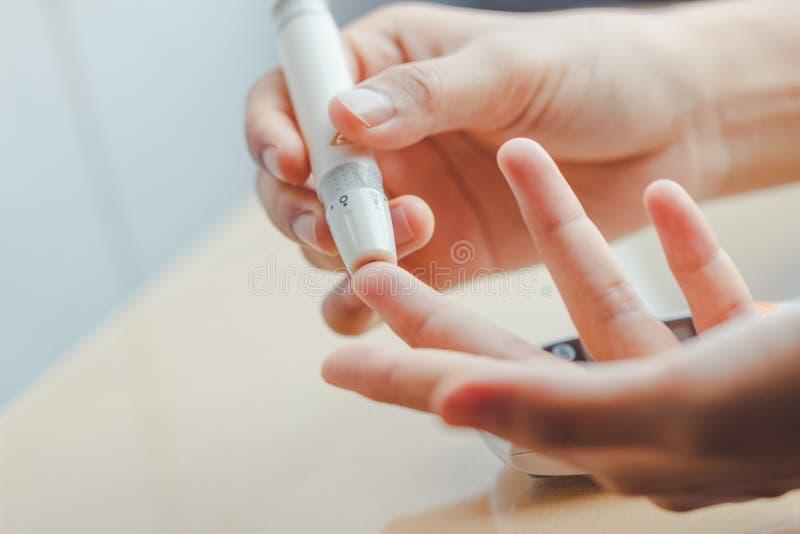 Feche acima das mãos da mulher usando a lanceta no dedo para verificar o nível do açúcar no sangue pelo medidor da glicose usando foto de stock