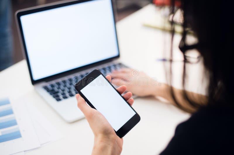 Feche acima das mãos da mulher usando o telefone celular e o laptop com a tela vazia do espaço da cópia para seu texto da propaga foto de stock
