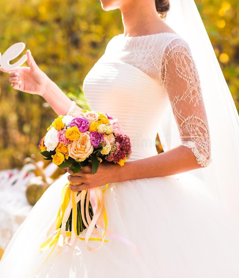 Feche acima das mãos da noiva que guardam o ramalhete bonito do casamento do outono imagens de stock