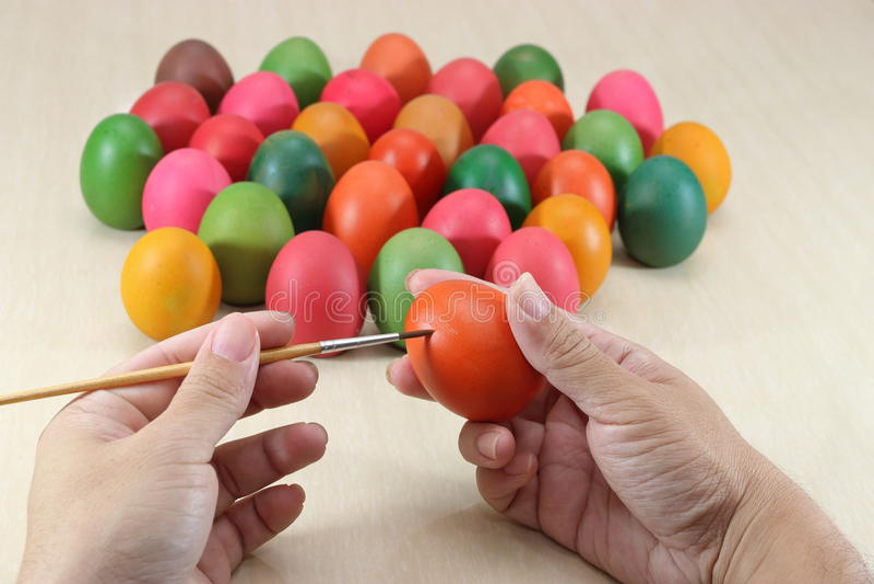 Feche acima das mãos de ovos coloridos da pintura cristã contra o pincel que prepara-se para o feriado de easter no fundo superio fotos de stock royalty free