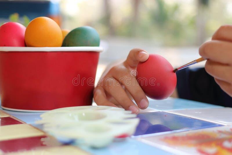 Feche acima das mãos de ovos da coloração da criança com o pincel para preparar o dia da Páscoa no fundo borrado natureza fotografia de stock royalty free