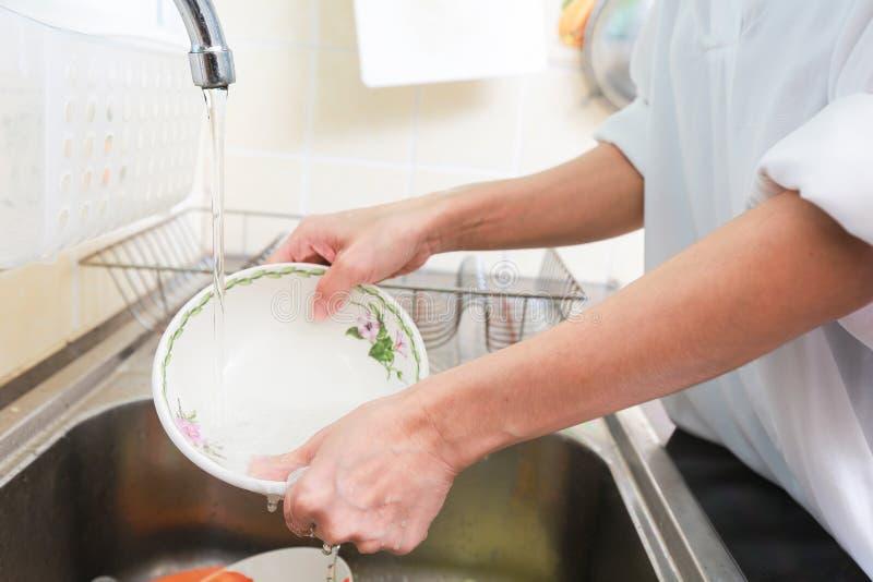 Feche acima das mãos de pratos de lavagem da mulher na cozinha foto de stock