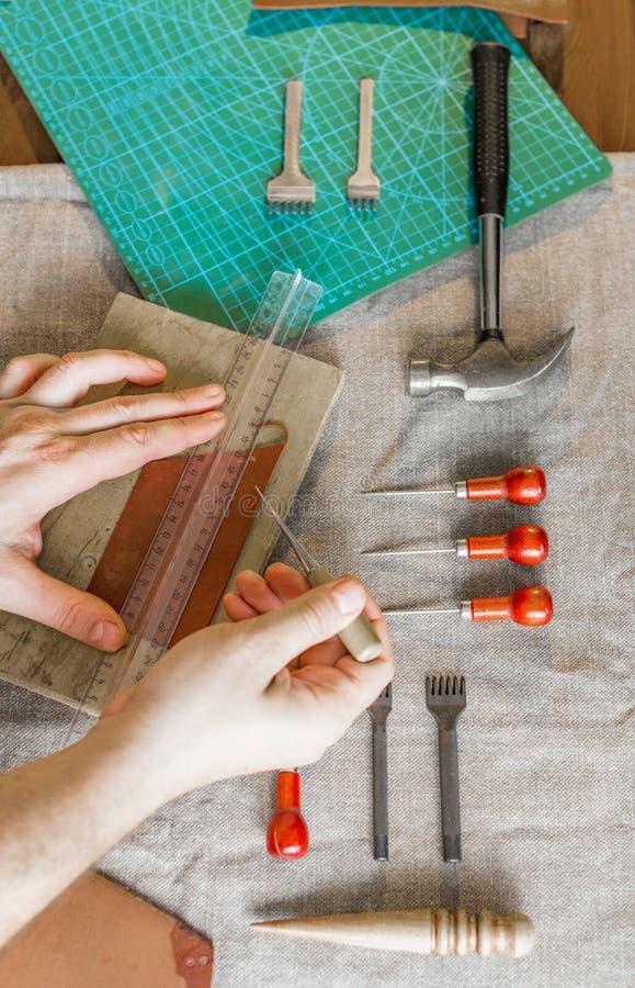 Feche acima das mãos de um artesão de couro que trabalha com matéria têxtil de couro em uma oficina imagens de stock