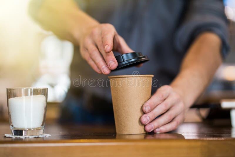 Feche acima das m?os de um barista que preparam o caf? para ir na cafetaria imagens de stock