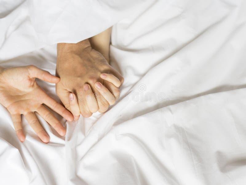 Feche acima das mãos de um par que tem o sexo em uma cama fotos de stock royalty free