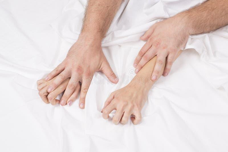 Feche acima das mãos de um par que tem o sexo em uma cama imagem de stock royalty free