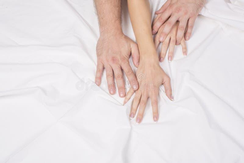 Feche acima das mãos de um par que tem o sexo em uma cama foto de stock royalty free
