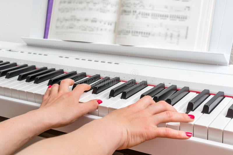Feche acima das mãos de uma jovem mulher que joga o piano imagens de stock