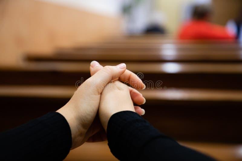 Feche acima das mãos de uma mulher que rezam na igreja foto de stock royalty free