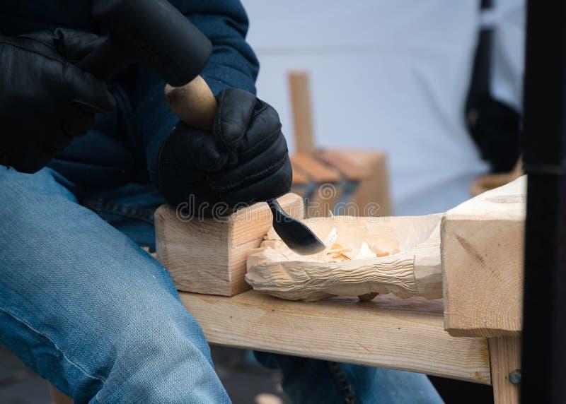 Feche acima das mãos do artesão cinzelam com uma goivadura nas mãos na bancada na carpintaria imagem de stock