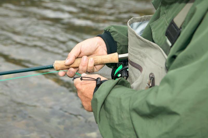 Feche acima das mãos, do carretel, da haste e da linha do pescador imagens de stock royalty free