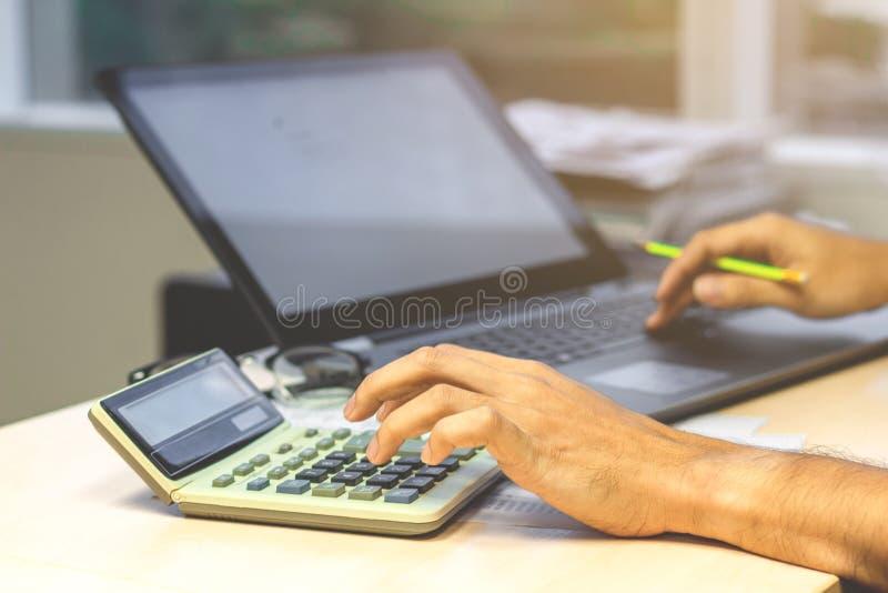 Feche acima das mãos do contador do homem de negócios que trabalham na calculadora imagens de stock royalty free