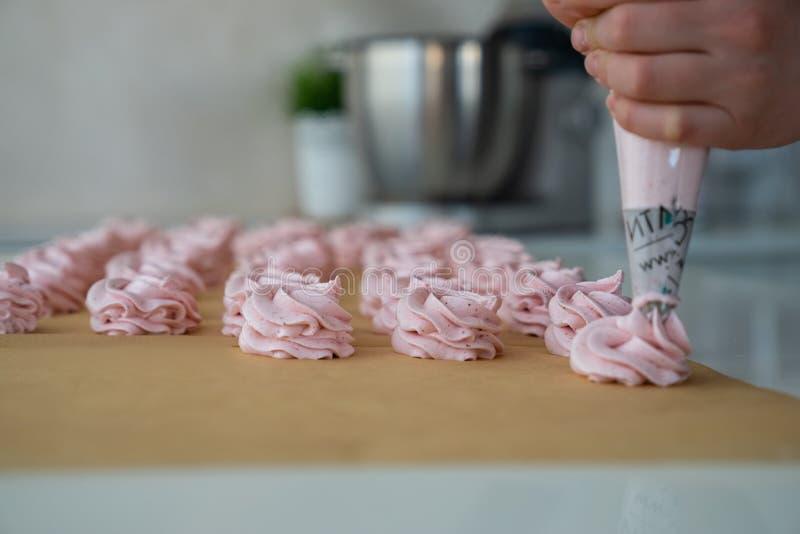 Feche acima das mãos do cozinheiro chefe com creme do saco dos confeitos ao papel de pergaminho na cozinha da loja de pastelaria fotografia de stock