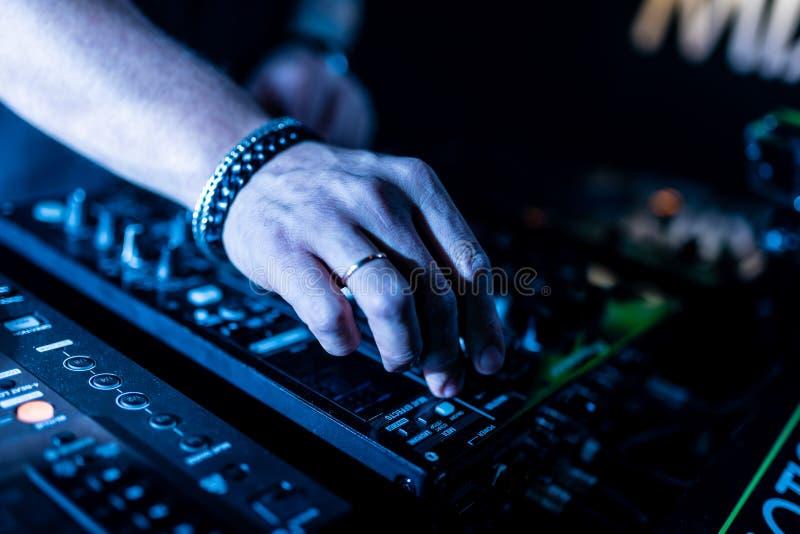 Feche acima das mãos do DJ que controlam uma tabela da música em um clube noturno fotos de stock