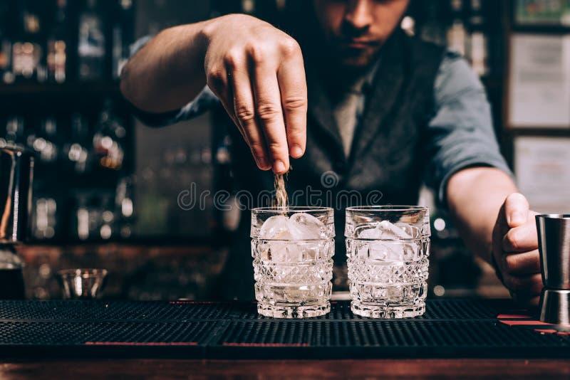Feche acima das mãos do empregado de bar que derramam o açúcar no cocktail antiquado bebidas frescas na barra foto de stock