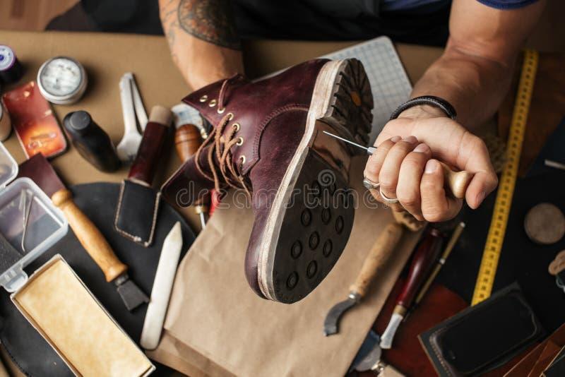 Feche acima das mãos do fabricante de sapata produzindo botas em sua oficina de couro imagens de stock