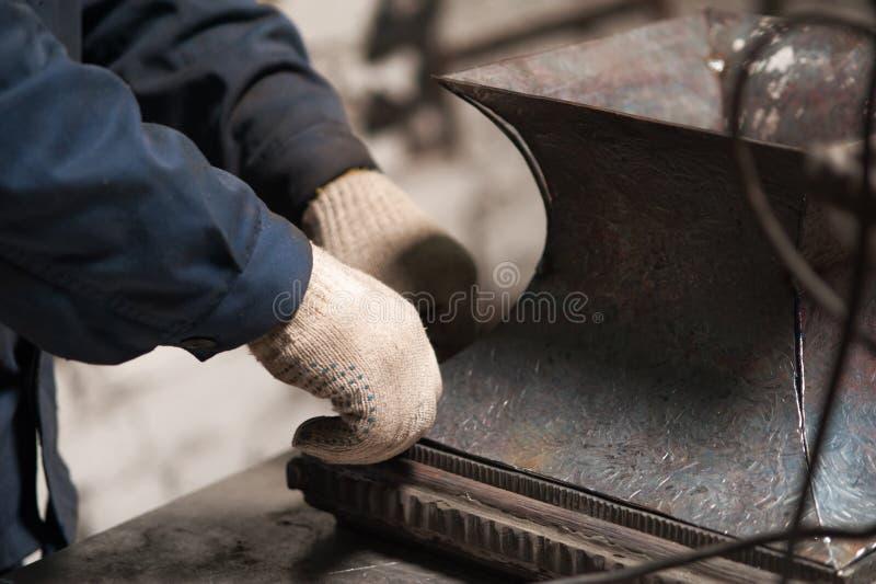 Feche acima das mãos do ferreiro e de uma placa de metal imagem de stock royalty free