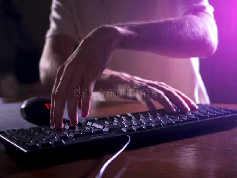 Feche acima das mãos do gamer no teclado que joga jogos de vídeo na noite imagens de stock