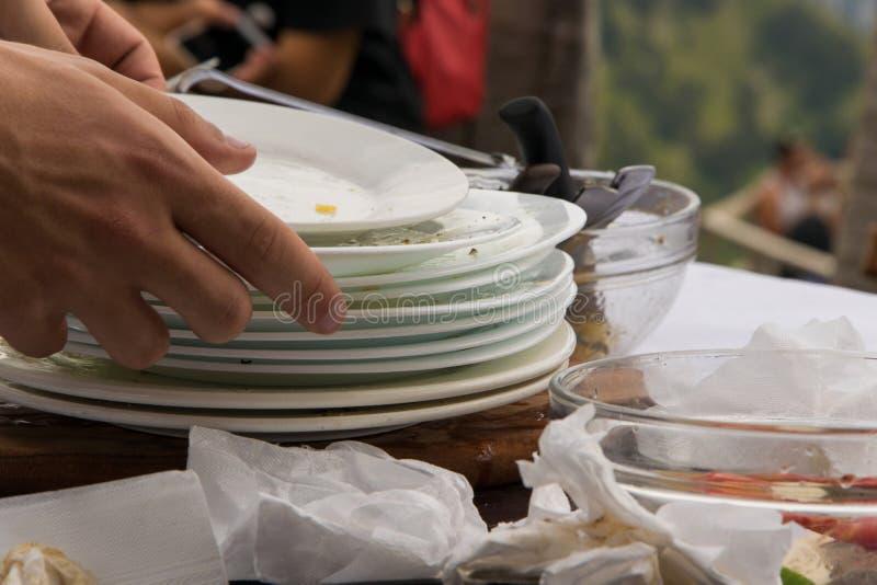 Feche acima das mãos do garçom que limpam a tabela dos pratos sujos foto de stock