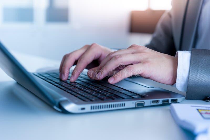Feche acima das mãos do homem de negócio que datilografam no laptop imagens de stock royalty free