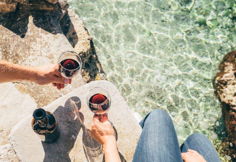 Feche acima das mãos do homem e da mulher da imagem com o cálice do vinho no SE imagens de stock royalty free