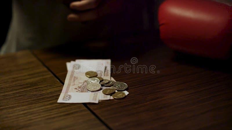 Feche acima das mãos do homem que guardam uma carteira de couro aberta com algumas moedas para dentro sobre uma tabela de madeira fotos de stock royalty free