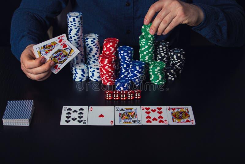 Feche acima das mãos do jogador de pôquer do homem novo que guardam cartões e microplaquetas na tabela do casino Conceito de jogo fotografia de stock royalty free