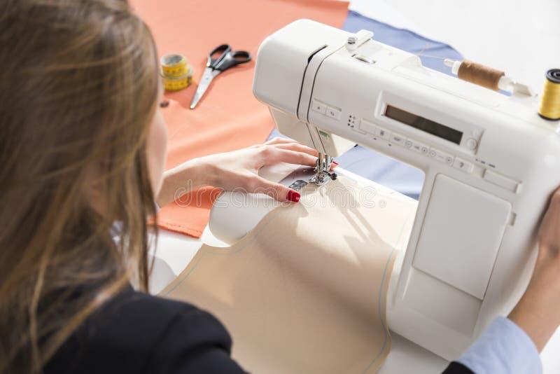 Feche acima das mãos do ` s da mulher usando uma máquina de costura foto de stock royalty free