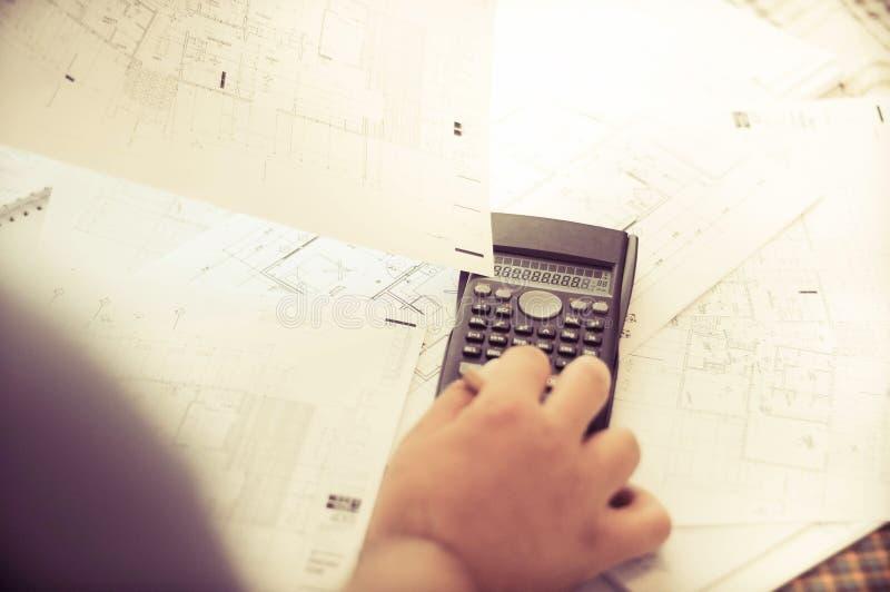 Feche acima das mãos dos coordenadores que trabalham na tabela, no ele esboço do projeto do desenho no canteiro de obras ou no es fotos de stock