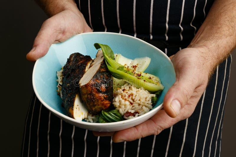 Feche acima das mãos dos cozinheiros chefe que apresentam uma bacia de galinha e de especiarias do empurrão imagens de stock