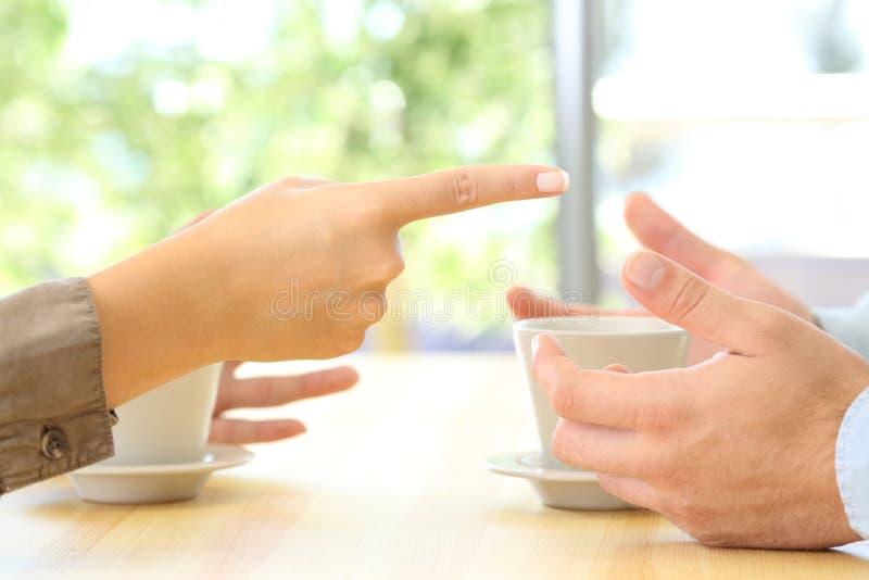 Feche acima das mãos dos pares que discutem em casa foto de stock