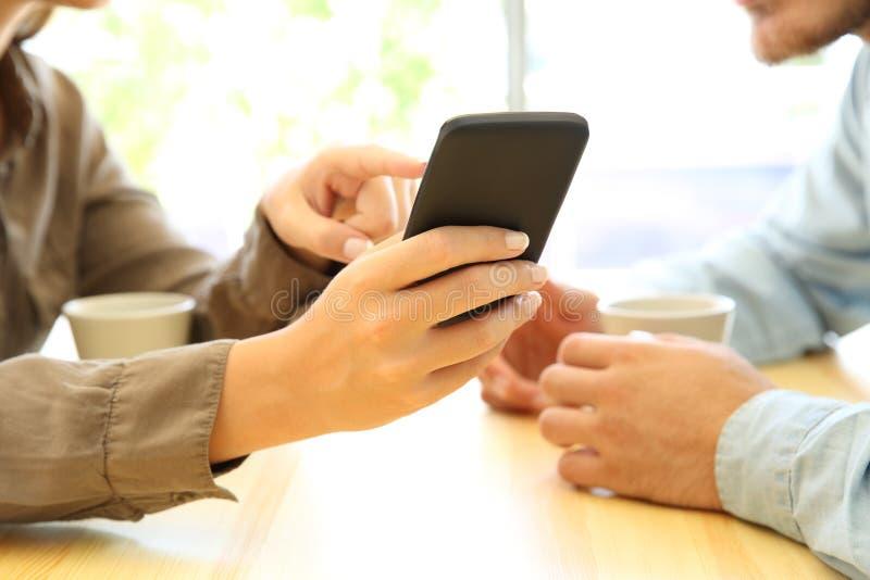 Feche acima das mãos dos pares usando um telefone esperto imagem de stock