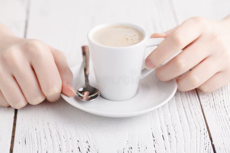 Feche acima das mãos fêmeas com a xícara de café na tabela Close up da ruptura de café fotos de stock