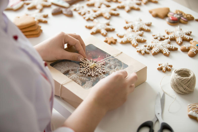 Feche acima das mãos fêmeas do pasteleiro que envolvem uma caixa fotos de stock royalty free