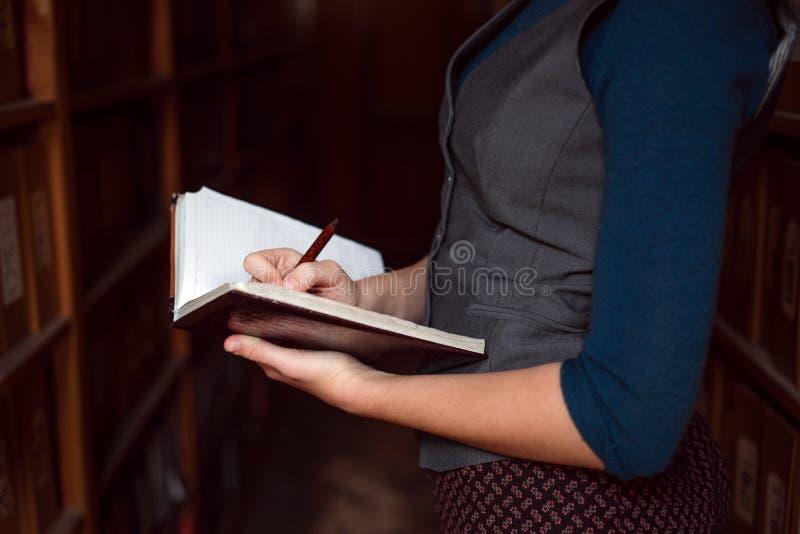Feche acima das mãos fêmeas que fazem anotações no caderno foto de stock royalty free