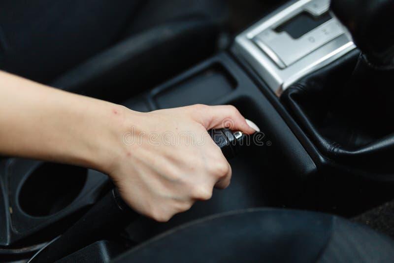 Feche acima das mãos fêmeas que guardam uma alavanca do handbrake para manter o veículo estacionário A menina põe o carro no parq imagens de stock royalty free