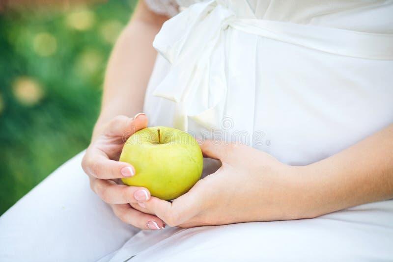 Feche acima das mãos humanas que guardam a barriga grávida e a maçã verde fotos de stock