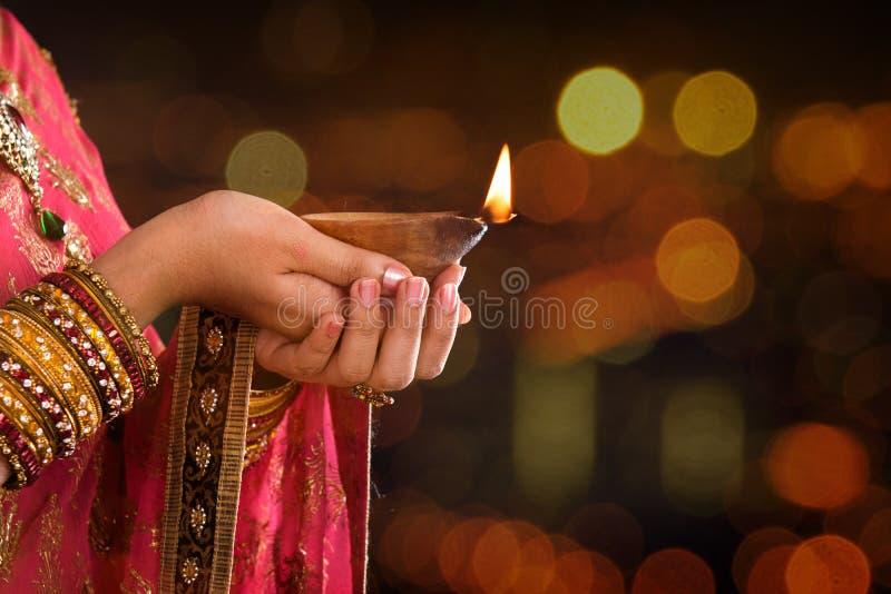 Feche acima das mãos indianas da mulher que guardam a luz do diya imagem de stock royalty free