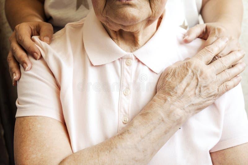Feche acima das mãos maduras da mulher & da enfermeira Cuidados médicos que dão, lar de idosos Amor parental da avó Doenças relat fotografia de stock royalty free