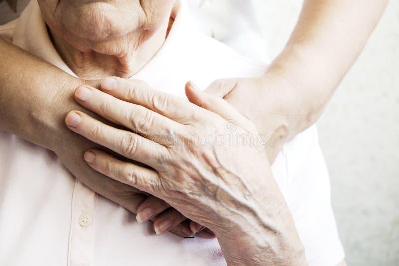 Feche acima das mãos maduras da mulher & da enfermeira Cuidados médicos que dão, lar de idosos Amor parental da avó Doenças relat imagens de stock