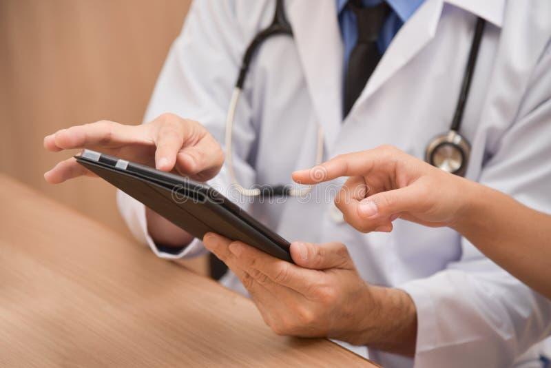 Feche acima das mãos masculinas asiáticas do doutor usando o tablet pc digital imagens de stock