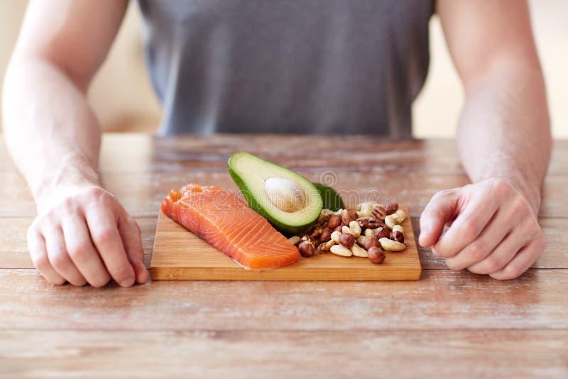 Feche acima das mãos masculinas com os ricos do alimento na proteína imagens de stock royalty free